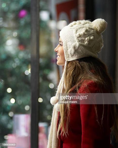 Woman looking in Christmas shop window.