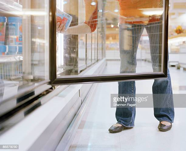 Woman looking in freezer at grocery store