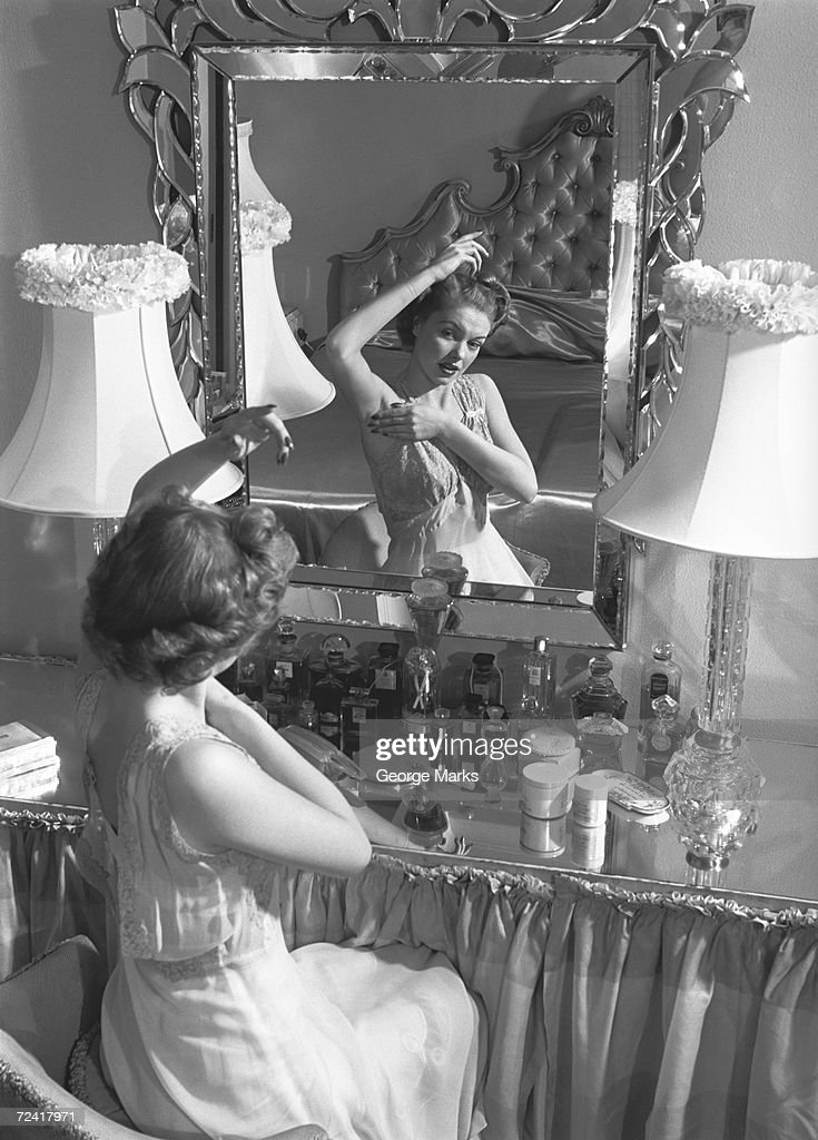 Woman looking in mirror, checking underarms (B&W)