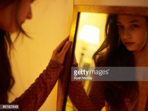 Woman looking in mirror.  : Stock Photo