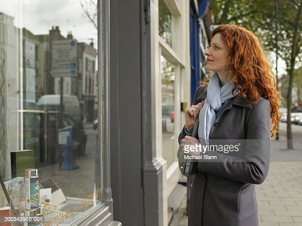 Woman looking in shop window, smiling, side view