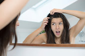 Horrified young woman looking in the bathroom mirror staring open mouthed at the first grey hair on her scalp, a first sign of ageing, or noticing that she is suffering from dandruff