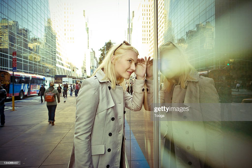 Woman looking in window of business : Stock Photo