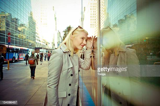 Woman looking in window of business