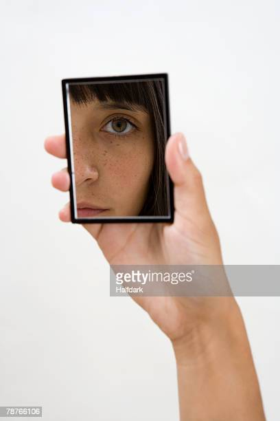 A woman looking into a hand mirror