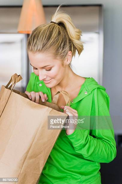 Woman looking into a paper bag