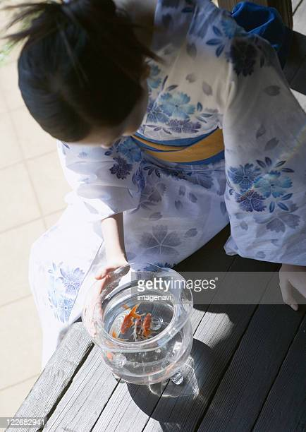 Woman looking into bowl of goldfish