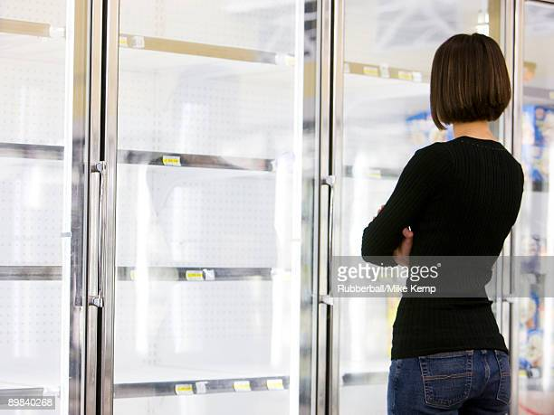 woman looking into empty refrigerators at market