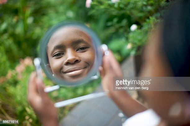 Woman looking into mirror in garden, Pietermaritzburg, KwaZulu-Natal Province, South Africa