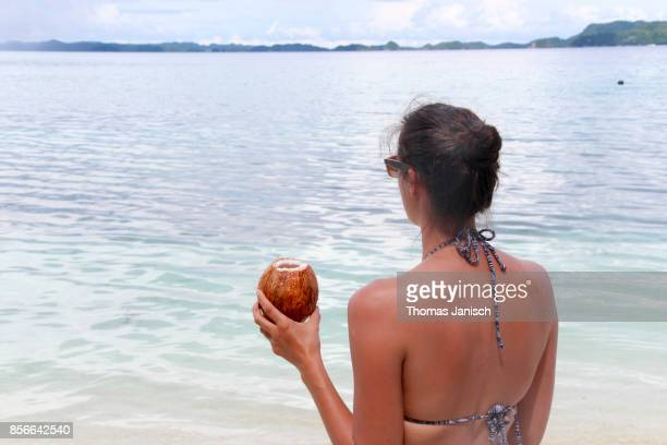Woman looking into the distance with a coconut drink in the hand, Palau