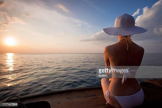 Donna guardando il tramonto da una barca