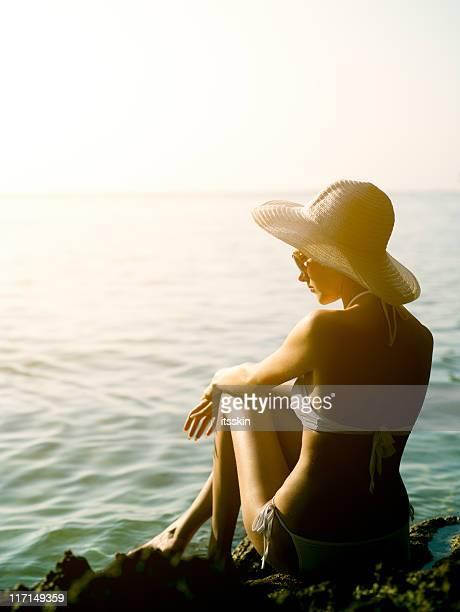 Donna guardando il tramonto da una roccia