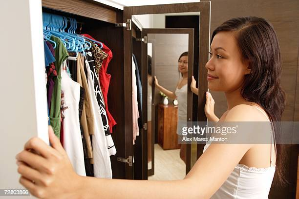 Woman looking into wardrobe full of clothes