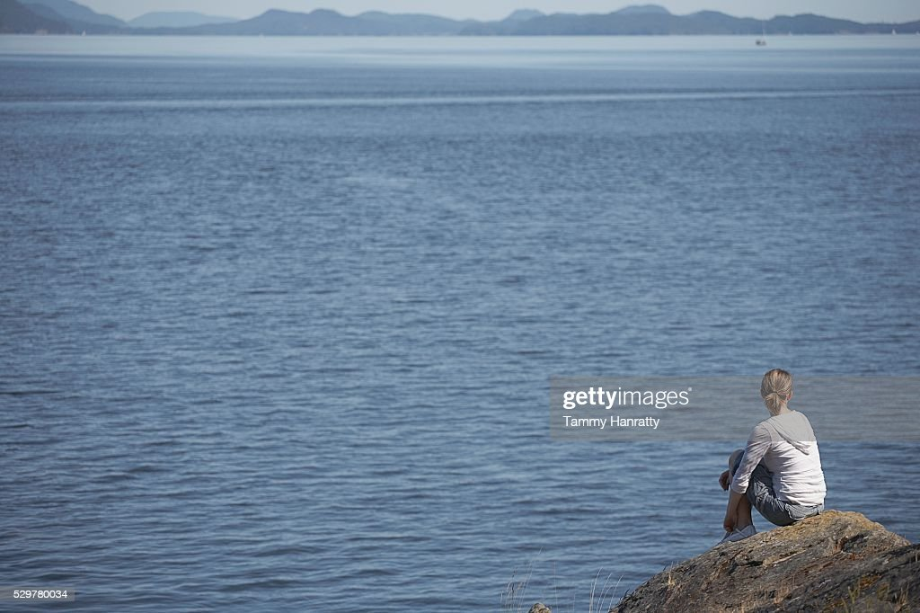 Woman looking out at bay : Stock Photo