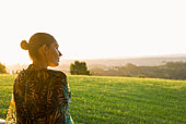 Woman looking out at hills at sunset
