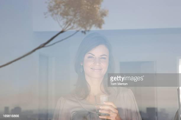 Frau schaut Wohnzimmer-Fenster