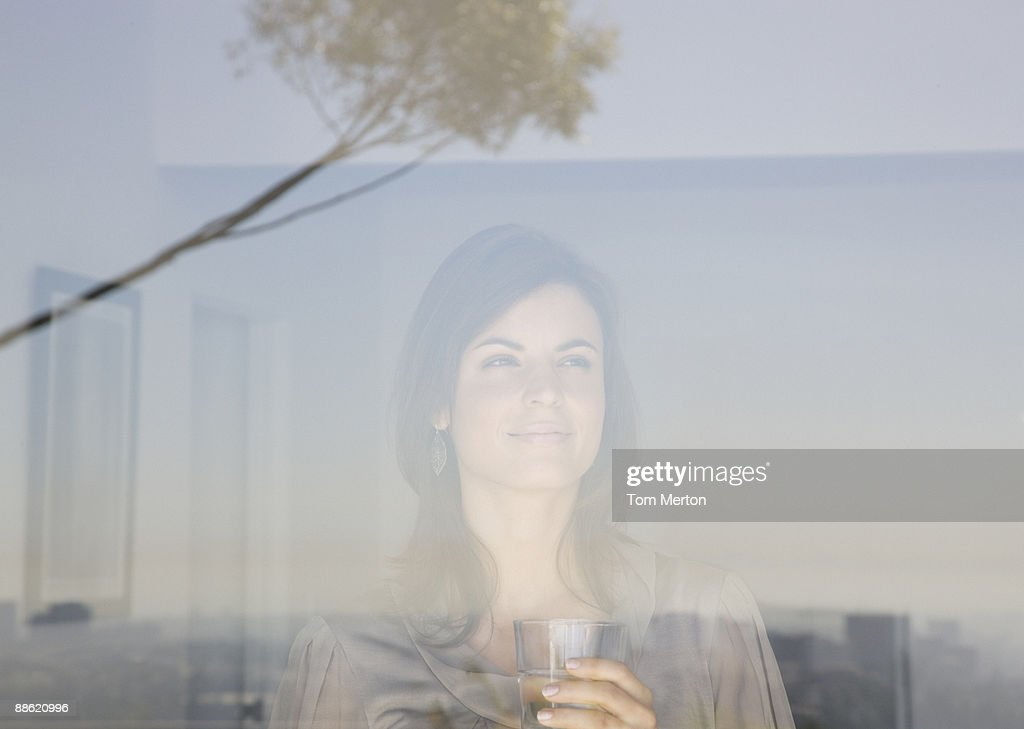 Woman looking out living room window : Stock Photo