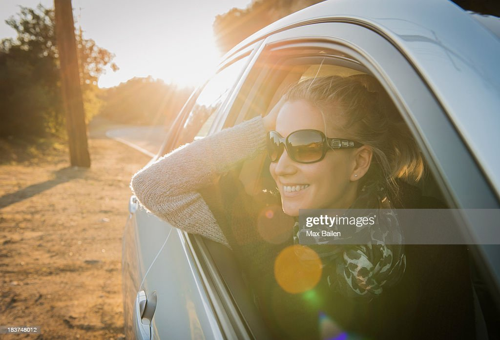 Woman looking out of car window : Stock Photo