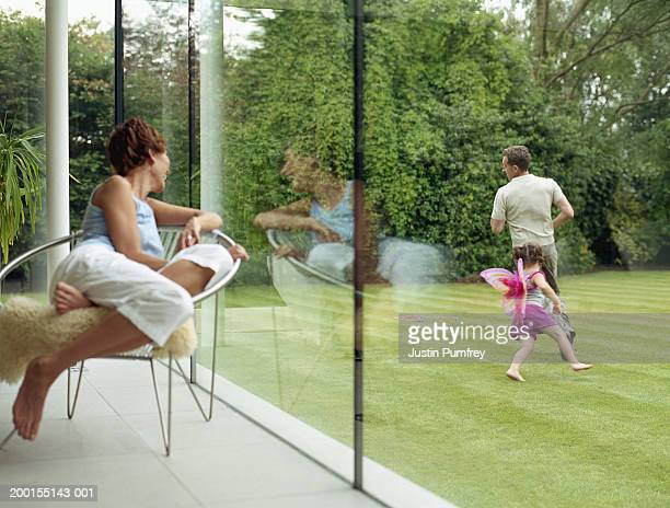 Woman looking out of window at father and daughter running in garden