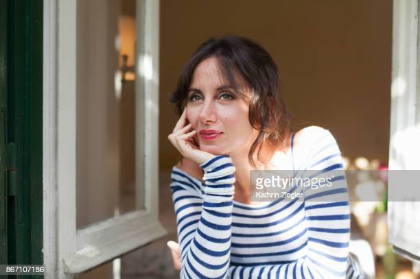 Woman looking out of window, smiling