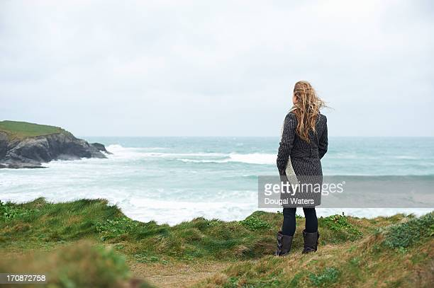 Woman looking out over Atlantic coastline.