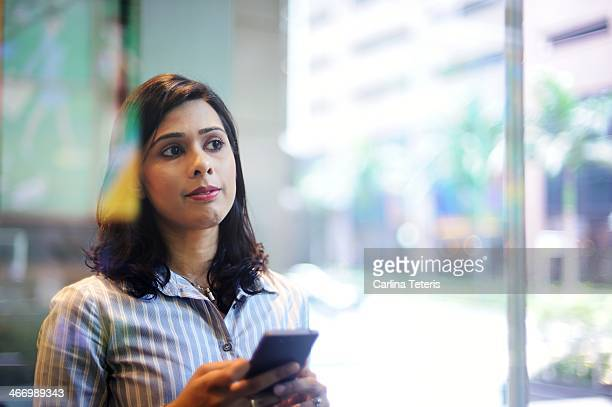 Woman looking out the window holding mobile phone