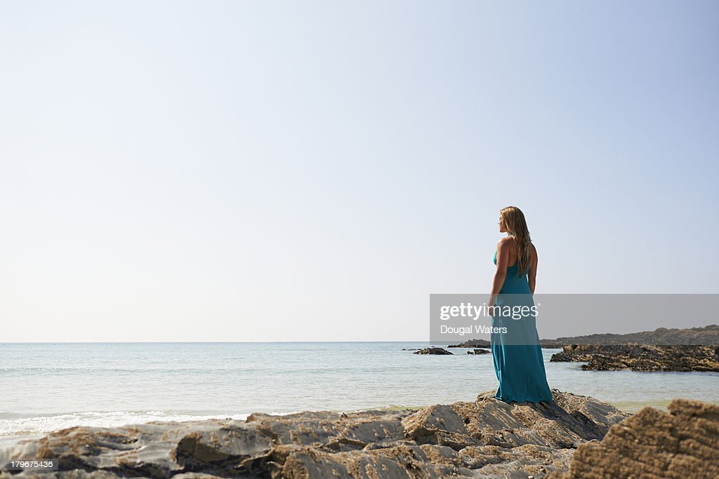 Woman looking out to sea on coastline. : Stock Photo