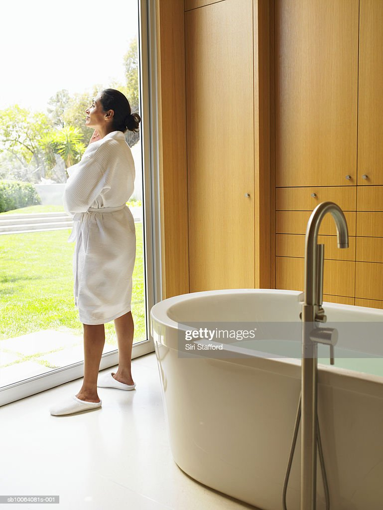 Woman looking out window in bathroom : Stock Photo