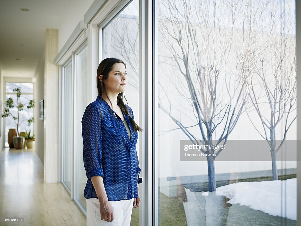 Woman looking out window in hallway of modern home : Stock Photo