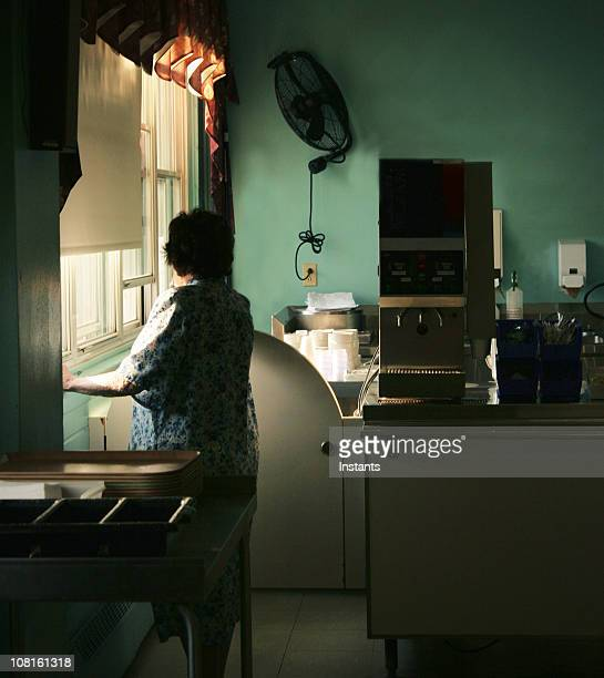 Woman Looking Out Window in Kitchen