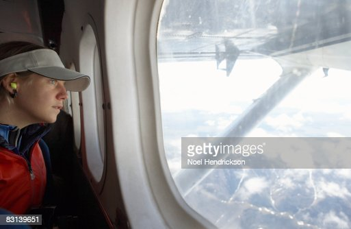 woman looking out window of aircraft : Stock Photo