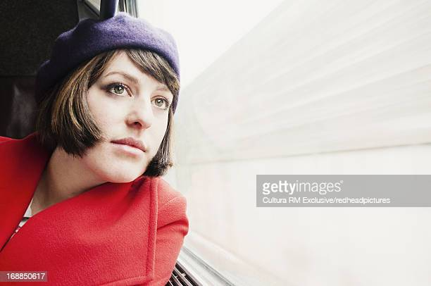 Woman looking out window on train
