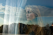 Woman looking out window with reflections