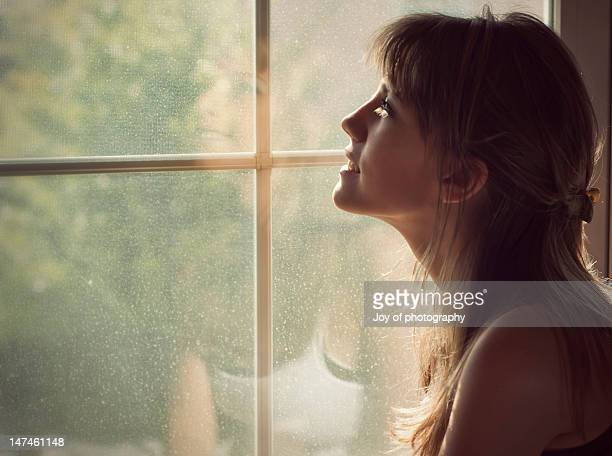 Woman looking outside from window