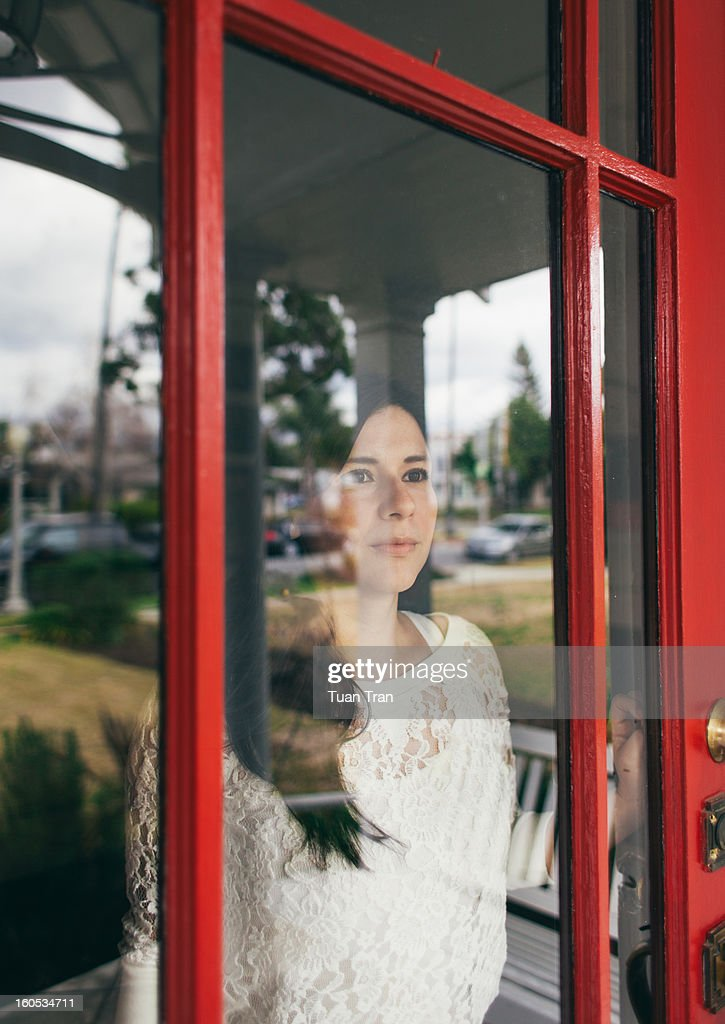 woman looking outside the house : Stock Photo