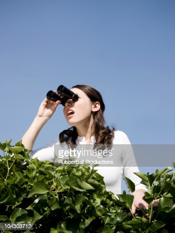 woman looking over a hedge with binoculars : Stock Photo