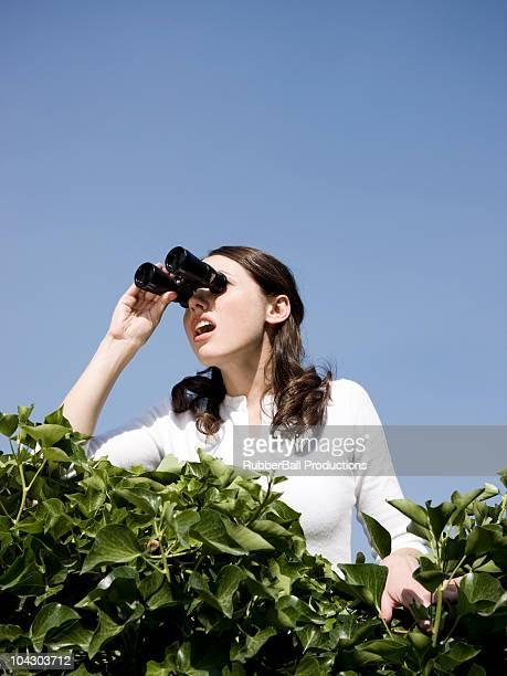 Frau über eine Hecke mit Fernglas