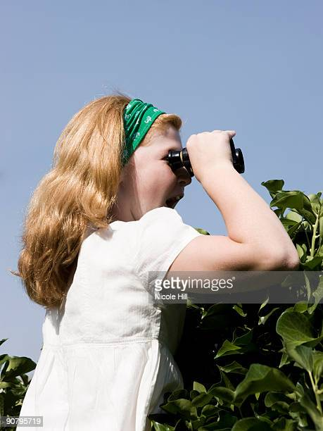woman looking over a hedge with binoculars