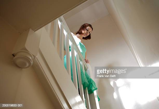 Woman looking over banisters, low angle view
