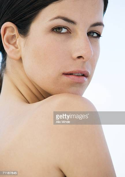 Woman looking over bare shoulder