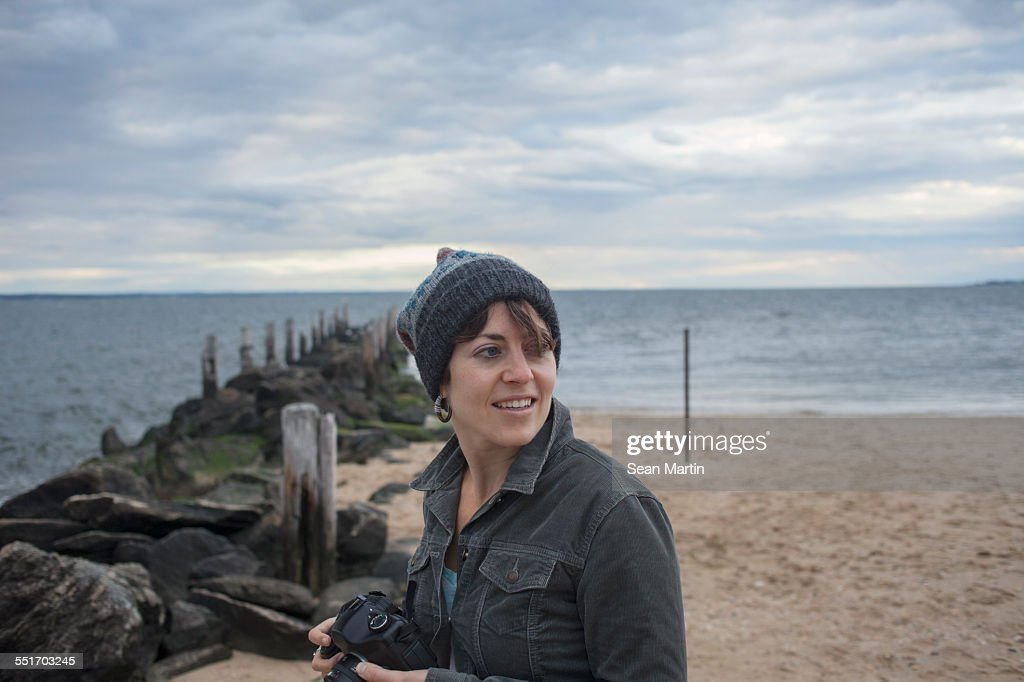 Woman looking over her shoulder whilst strolling on beach, Long Island, Brooklyn, New York, USA