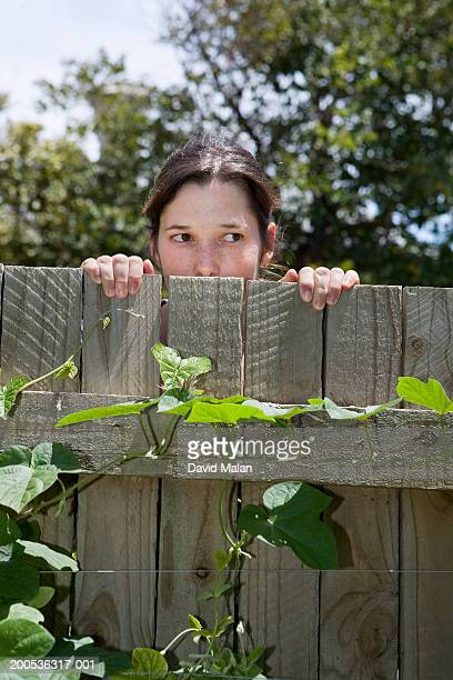 Woman looking over wooden fence