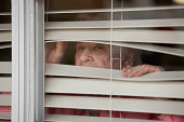 Elderly lady peering through a set of closed blinds.