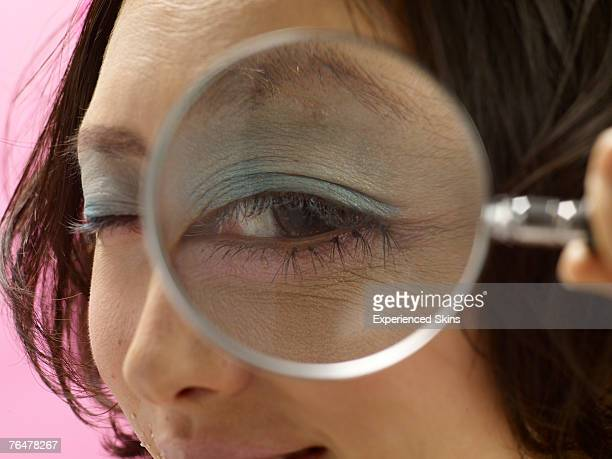 Woman looking through a magnifying glass, close-up