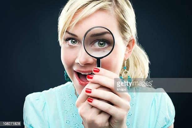 Donna guardando attraverso una lente di ingrandimento