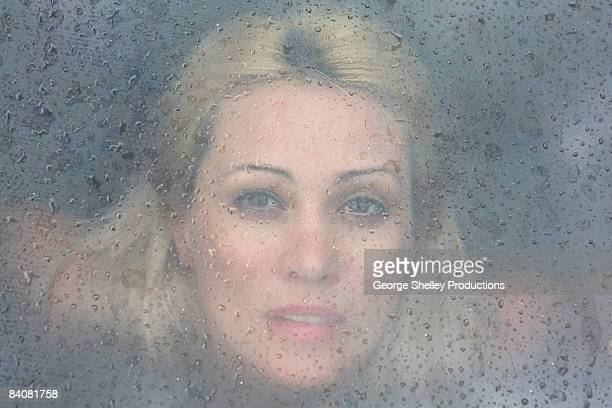 Woman looking through a rain drop window