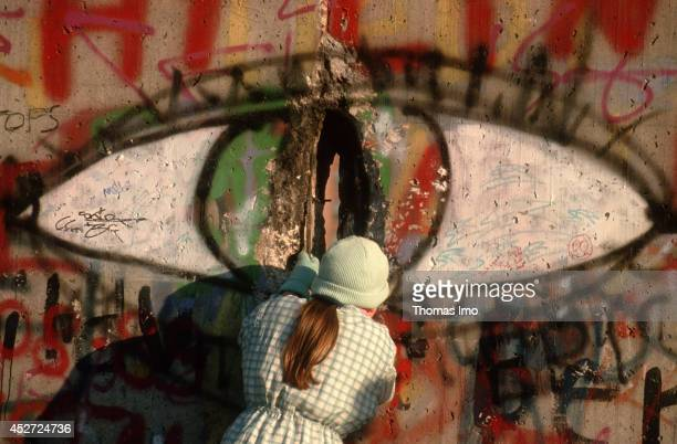 Woman looking through a whole of the Berlin Wall after opening of the border on November 09 in Berlin Germany The year 2014 marks the 25th...