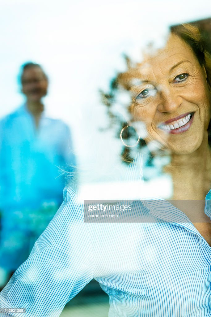Woman looking through a window : Stock Photo