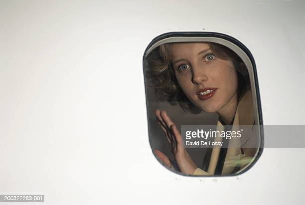 Woman looking through airplane's window, view from outside