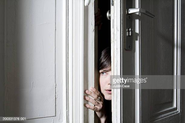 Woman looking through ajar door